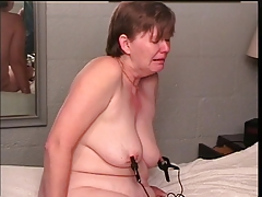 Chunky short-haired blonde submits to clamps on her nipples and coochie